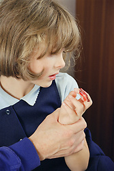 Young girl looking at finger wound,