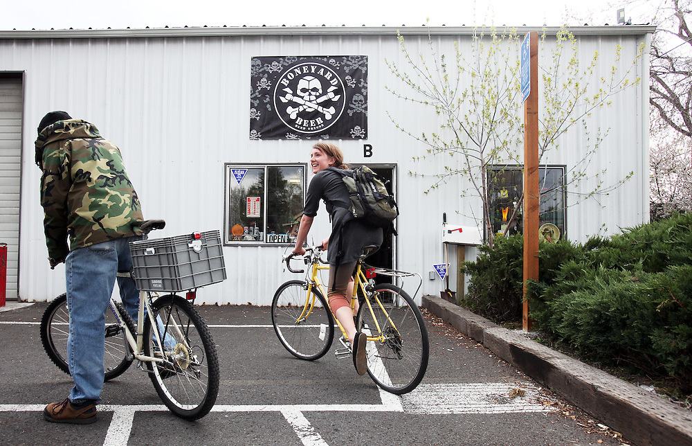 Backpack loaded with growlers of beer, Kaysie Patka bikes away from Boneyard Brewing. Craft beer permeates the culture in Central Oregon city of Bend, with 10 breweries serving pints, growlers and kegs to a community of less than 90,000. Photographed Wednesday, April 25, 2012. Assignment ID 30125094A