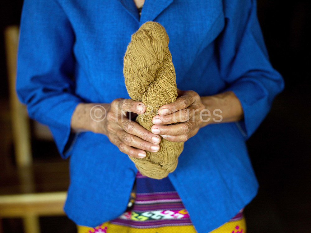 A Tai Lue ethnic minority woman holds a skein of naturally coloured brown cotton, Ban Bimi, Sayaboury province, Lao PDR.  The Tai Lue are known as expert weavers particularly of cotton which they cultivate locally. One of the most ethnically diverse countries in Southeast Asia, Laos has 49 officially recognised ethnic groups although there are many more self-identified and sub groups. These groups are distinguished by their own customs, beliefs and rituals.