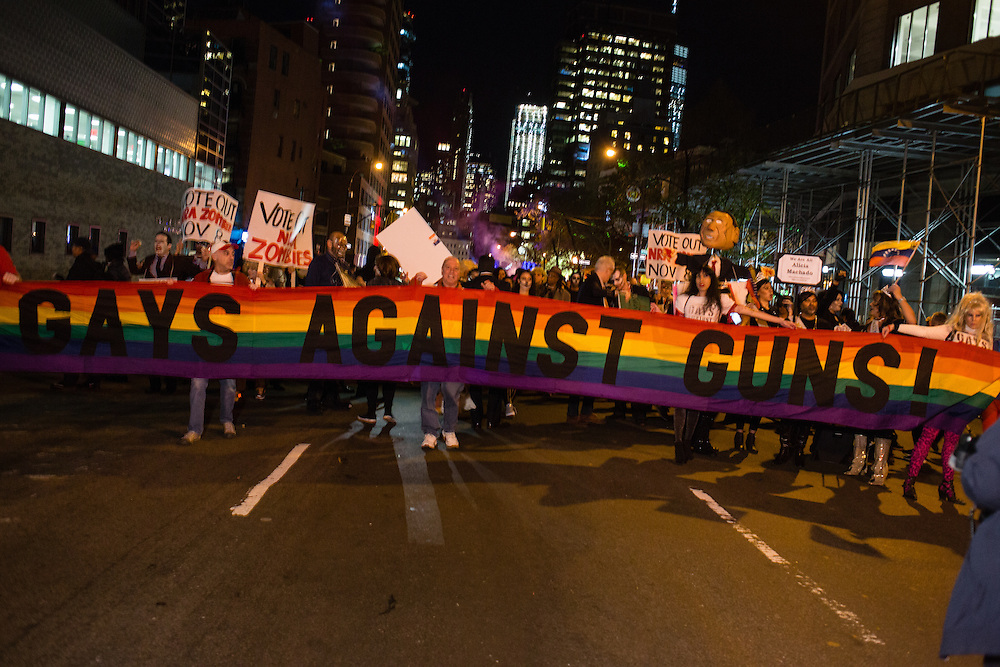 """New York, NY - 31 October 2016. GFays Against Guns marching beind their banner in the Greenwich Village Halloween Parade. The parade's theme was """"Reverie"""", but a number of individuals and groups had political messages."""