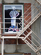 """24 MARCH 2020 - DES MOINES, IOWA: A cardboard cutout of a NFL official wearing a mask in the window of an apartment in downtown Des Moines. On Tuesday morning, 24 March, Iowa reported over 120 confirmed cases of the Coronavirus (SARS-CoV-2) and COVID-19. Restaurants, bars, movie theaters, places that draw crowds are closed for at least 30 days. The Governor has not ordered """"shelter in place""""  but several Mayors, including the Mayor of Des Moines, have asked residents to stay in their homes for all but the essential needs. People are being encouraged to practice """"social distancing"""" and many businesses are requiring or encouraging employees to telecommute.         PHOTO BY JACK KURTZ"""