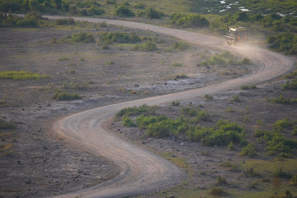 Game drive vehicle on dusty winding road, Amboseli National Park, Kenya, Africa