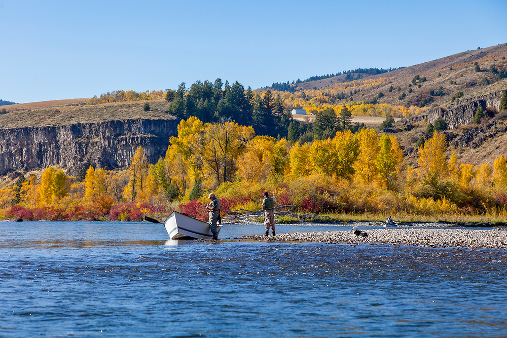 Two Fly Fishermen and a dog enjoy a brilliant autumn day fishing on the South Fork of the Snake River near Heise Hot Springs in Eastern Idaho