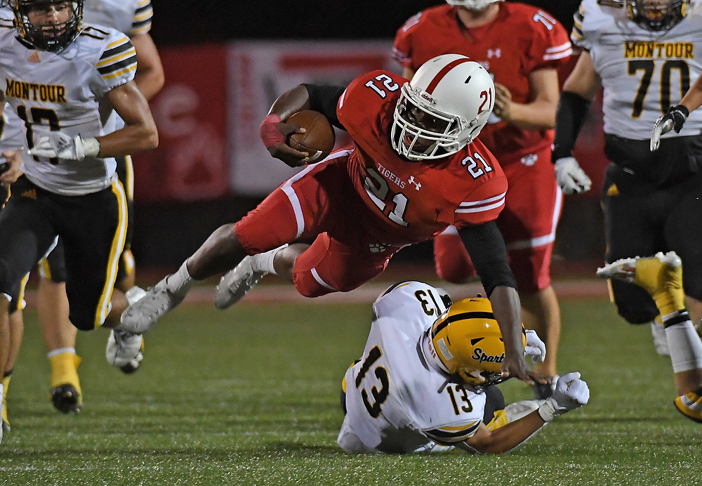 Joe Cotton #21 of the Moon Tigers goes airborne after being hit by Michael Captline #13 of the Montour Spartans in the second half during the game at Tiger Stadium on September 3, 2021 in Moon Township, Pennsylvania.