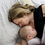 A nine month old baby girl is cuddled by her mother while asleep in bed together. Photo Tim Clayton