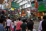 Many pedestrians cross a busy street crossing near to old fashioned advertising signs in Wan Chai district of Hong Kong, China. Wan Chai is a busy shopping area, close to Central. The people walking in this area are almost all Chinese, the area far less westernised than very nearby Central.