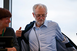 © Licensed to London News Pictures. 31/08/2016. London, UK. Leader of the opposition and Labour leadership candidate JEREMY CORBYN takes off his jacket before speaking to outline how his policy agenda benefits women on 31 August 2016 at Unison Centre, London. Photo credit: Tolga Akmen/LNP