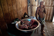 Indigenous man with a bowl of butchered pig. A third of Altamira in the state of Para, Brazil will be flooded to make way for the Belo Monte dam, nearly all the people affected are the poorest in society or indigenous communities that will have nowhere to go if they were made homeless, and the Government payoff for their properties is low therefore making it difficult to find new accomodation. At present, the Arara land is protected from development, sale or new residents as it has been their ancestral land for hundreds of years, this is now one of the key areas under threat
