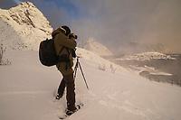 Photographer in winter photographs over village of Reine, Moskenesøy, Lofoten Islands, Norway
