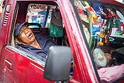 """26 SEPTEMBER 2012 - BANGKOK, THAILAND:  A truck driver sleeps in the cab of his truck in Khlong Toey Market in Bangkok. Khlong Toey (also called Khlong Toei) Market is one of the largest """"wet markets"""" in Thailand. The market is located in the midst of one of Bangkok's largest slum areas and close to the city's original deep water port. Thousands of people live in the neighboring slum area. Thousands more shop in the sprawling market for fresh fruits and vegetables as well meat, fish and poultry.    PHOTO BY JACK KURTZ"""