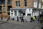 As the UKs Coronavirus death toll during the governments social distancing lockdown, rose by 384 to 33,998, and the R rate of infection is reported to be between 0.7 and 1.0, south Londoners queue around the corner of  Pensose Street and Walworth Road to access the branch of Barclays Bank, on 15th May 2020, in London, England.
