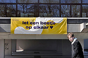 Nederland, Nijmegen, 4-4-2020  Tegen de gevel van de schouwburg, stadsschouwburg, heeft men een spandoek gespannen met de tekst: Let een beetje op elkaar, als advies naar de passanten op straat tijdens de coronacrisis.Foto: Flip Franssen