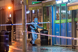 © Licensed to London News Pictures. 14/12/2020. London, UK. A forensic investigator carrying a tripod walks into a shop entrance on Station Road. Police were called at approximately 19:15GMT on Sunday, 13 December to reports of a stabbing in St Anns Road, Harrow. Officers and London Ambulance Service attended. <br /> A man – believed aged in his 20s – was found suffering stab injuries; despite the efforts of the emergency services he was pronounced dead at the scene. Two further males – both believed aged in their late teens – also suffered stab injuries. Photo credit: Peter Manning/LNP