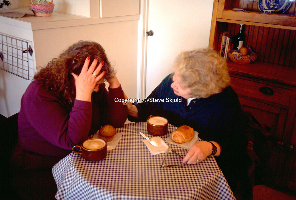 Sister age 58 consoling sister age 54 over coffee.  St Paul  Minnesota USA