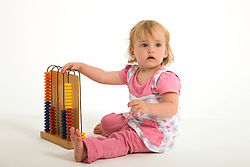 Little girl in the studio playing with an abacus,