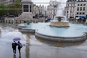 A couple walk past the fountains in a quiet Trafalgar Square during seasonal Spring rainfall, on 24th May 2021, in London, England.