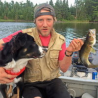 Ben Wiltsie displays a walleye he caught while fishing with his dog Evie.