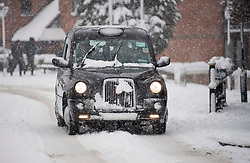 © Licensed to London News Pictures. 10/12/2017. Tring, UK. A black cab makes it's way through heavy snow in Tring, Buckinghamshire, England as parts of the south east of England are blanketed with snow for the first time this winter. Photo credit: Ben Cawthra/LNP