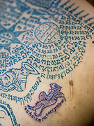"07 MARCH 2015 - NAKHON CHAI SI, NAKHON PATHOM, THAILAND: Detail photo of Sak Yant tattoos on a man's back at the Wat Bang Phra tattoo festival. Wat Bang Phra is the best known ""Sak Yant"" tattoo temple in Thailand. It's located in Nakhon Pathom province, about 40 miles from Bangkok. The tattoos are given with hollow stainless steel needles and are thought to possess magical powers of protection. The tattoos, which are given by Buddhist monks, are popular with soldiers, policeman and gangsters, people who generally live in harm's way. The tattoo must be activated to remain powerful and the annual Wai Khru Ceremony (tattoo festival) at the temple draws thousands of devotees who come to the temple to activate or renew the tattoos. People go into trance like states and then assume the personality of their tattoo, so people with tiger tattoos assume the personality of a tiger, people with monkey tattoos take on the personality of a monkey and so on. In recent years the tattoo festival has become popular with tourists who make the trip to Nakorn Pathom province to see a side of ""exotic"" Thailand.   PHOTO BY JACK KURTZ"