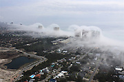 Spectacular 'cloud tsunami' rolls over Florida high-rise condos<br /> <br /> Breathtaking images of 'wave clouds' were captured by a helicopter pilot as they rolled off the sea and inland, completely engulfing a beachfront city.<br /> The surreal event was captured by helicopter pilot Mike Schaeffer who was just finishing a tour of the coastline in Panama City Beach, Florida when he spotted the weather phenomenon - called a Kelvin–Helmholtz instability.<br /> The cloud swept across the sands creating a tsunami effect and over the top of the roofs of the beachfront blocks of condos earlier this month<br /> It normally occurs in regions with vast plains where winds quickly change speed creating turbulence but appeared in the beachfront city on February 5.  <br /> A fast-moving, lighter density cloud slides on top of a slower, thicker layer, dragging out the surface and creating the wave effect.<br /> <br /> The Cloud Appreciation Society explains the quirky weather phenomenon. They are the result of turbulence in a layer of Cirrus cloud where air currents exist of differing speeds or directions - making the cloud resemble a wave rolling along the top of the water. <br /> The incredibly uncatchy name is a combination from Lord Kelvin - a Scottish baron who along with a German physicist Hermann Helmholtz - came up with an explanation for the freak occurrence. <br /> ©JR Hott / Exclusivepix