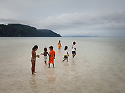Kids looking for shells at low tide. On Mantabuan island.