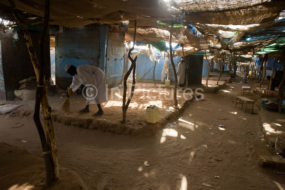 A man sweeps his own area where he sells food in the 4 sq km Abu Shouk refugee camp which is (disputedly) home to 38,000 displaced persons and families on the outskirts of the front-line town of Al Fasher (also spelled, Al-Fashir) in north Darfur. The camp has 17 schools, clinics and commercial activity  based around a market, furniture manufacture and variety of cottage industries. The camp has 17 schools, clinics and commercial activity  based around a market, furniture manufacture and variety of cottage industries and a third of families in the camps are headed by women.
