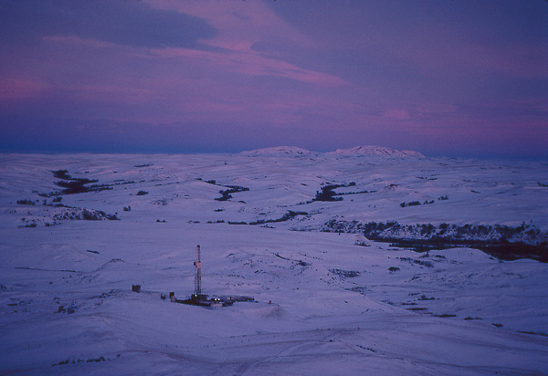 Stock photo of an aerial evening view of an on-shore oil and gas drilling rig site in the snow