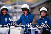 Three young schoolkids smile as they ride their bikes home from school in Japan