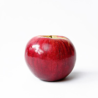 Still life of a shiny red Macintosh apple on a white background with room for text.