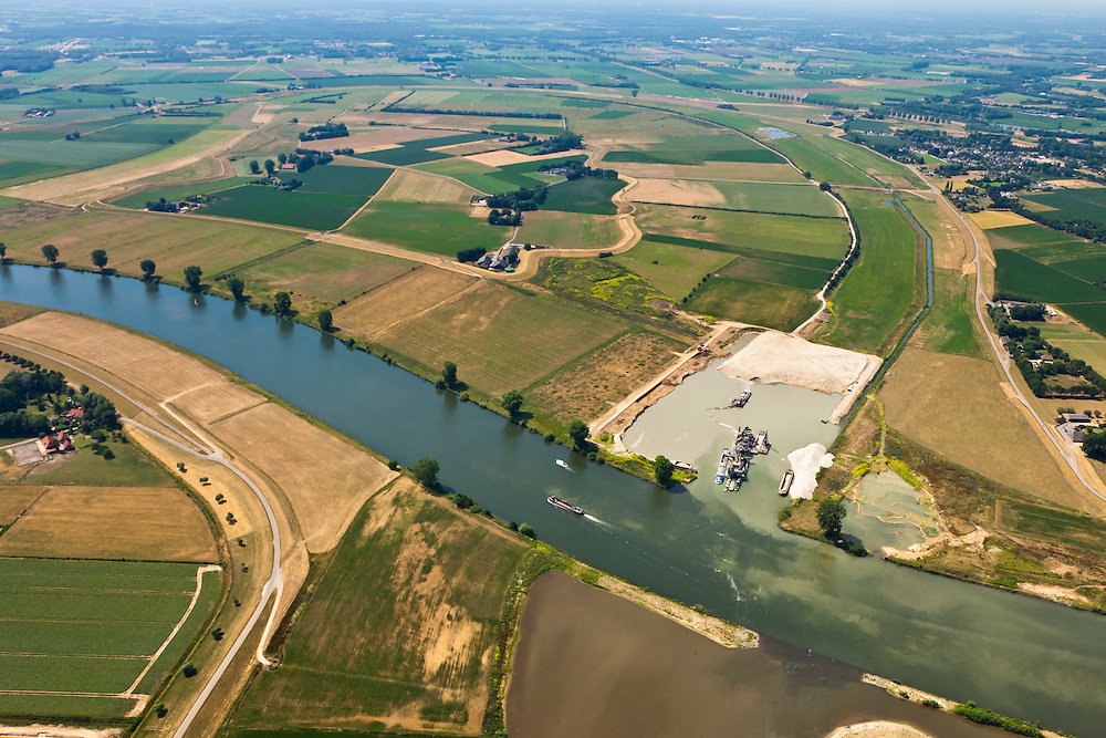 Nederland, Noord-Brabant, Gemeente Oss, 08-07-2010. Keent, Maas met Keentsche Uiterwaard. De oorspronkelijk meander is in het kader van de Maasnormalisatie (kanalisatie) afgesneden. Dit naar aanleiding van de watersnood in het rivierengebied in 1926. Inmiddels wordt de oude rivierarm weer uitgegraven en aan één zijde met de Maas verbonden om bij hoogwater meer water uit de Maas te kunnen bergen..Meuse with Keent floodplain. The original meander has been cut during the Meuse Standardization (canalisation). This was done in response to the floods in 1926. Meanwhile, the old river arm is being excavated and one sided is reconnected to the river to create storage for water during high water..luchtfoto (toeslag), aerial photo (additional fee required).foto/photo Siebe Swart
