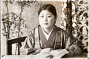 studio portrait of a young adult female student with book Japan ca 1930s