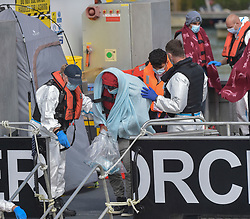 © Licensed to London News Pictures. 17/09/2021. Dover, UK.  Border force officials assist migrants as they arrive at Dover Harbour in Kent. Migrants are continuing to attempt the crossing from France as the weather improves this week. Photo credit: Stuart Brock/LNP