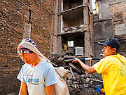 02 MARCH 2017 - SANKHU, NEPAL: Laborers dig out a destroyed home in the shadow of a building being rebuilt in Sankhu, one of the Nepalese communities hurt by the 2015 earthquake. There is more construction and rebuilding going on in Sankhu, west of central Kathmandu, than in many other parts of the Kathmandu Valley nearly two years after the earthquake of 25 April 2015 that devastated Nepal. In some villages in the Kathmandu valley workers are working by hand to remove ruble and dig out destroyed buildings. About 9,000 people were killed and another 22,000 injured by the earthquake. The epicenter of the earthquake was east of the Gorka district.   PHOTO BY JACK KURTZ