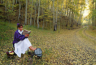 Colorado, woman reading book amidst autumn foliage, <br /> MODEL RELEASED