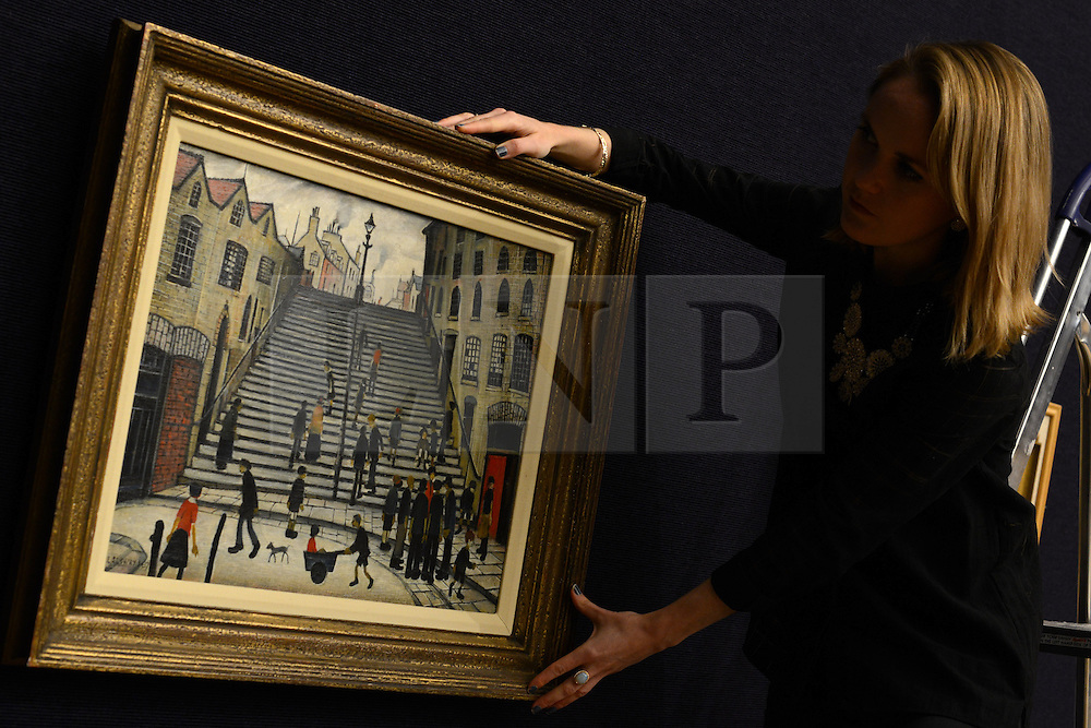 © Licensed to London News Pictures.14/11/2013. London, UK. A Bonhams employee arranges Laurence Stephen Lowry's 'The Steps at Wick' painting which expected to fetch over £800,000 of an auction in Bonhams on November 20.Photo credit : Peter Kollanyi/LNP