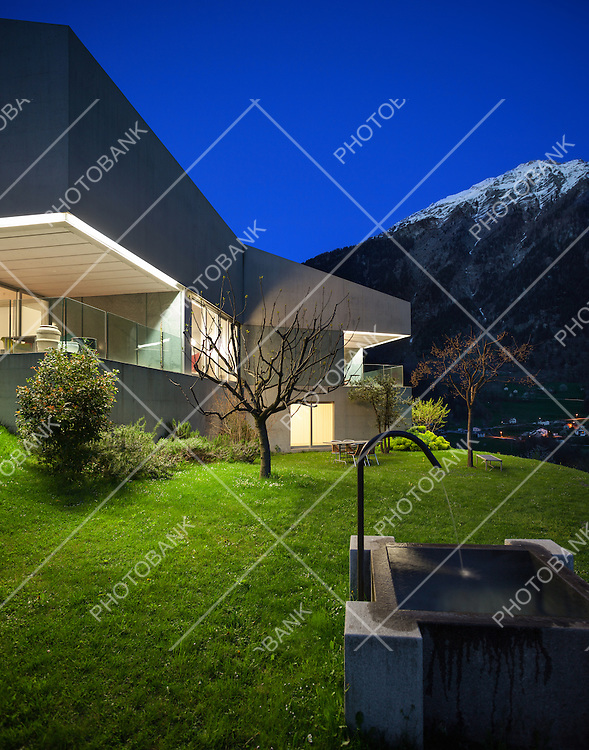 Architecture, concrete house with stone fountain, night scene