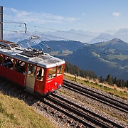 "A tourist train called the ""Rigibahn"" taking tourists down from sightseeing on Mount Rigi in the Swiss Alps."