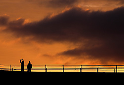 © Licensed to London News Pictures. <br /> 30/10/2016. <br /> Saltburn-by-the-Sea, UK.  <br /> A couple take a picture as they stand on the pier as the sun begins to rise over Saltburn-by-the-Sea on the north east coast of England.<br /> Photo credit: Ian Forsyth/LNP
