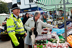 Policeman talking to members of the public in local market; Knaresborough; Scarborough; Yorkshire UK