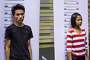 """17 JULY 2014 - BANGKOK, THAILAND: Undocumented Cambodian workers stand up for """"mug shots"""" for their temporary ID cards at the temporary """"one stop service center"""" in the Bangkok Youth Center in central Bangkok. Thai immigration officials have opened several temporary """"one stop service centers"""" in Bangkok to register undocumented immigrants and issue them temporary ID cards and work permits. The temporary centers will be open until August 14.    PHOTO BY JACK KURTZ"""
