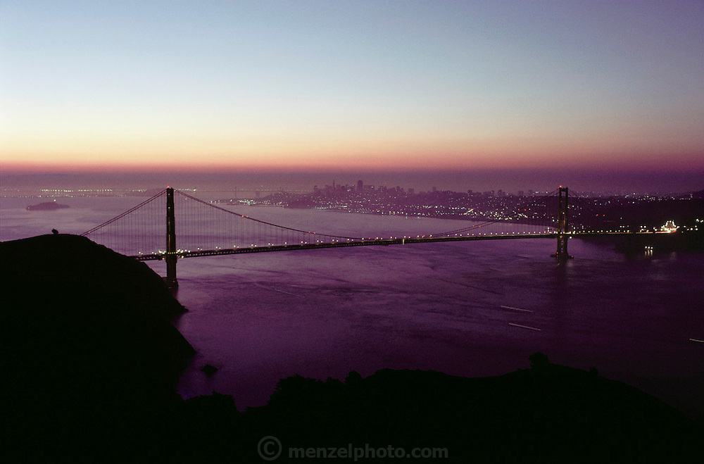 Golden Gate Bridge at sunrise; view from Marin Headlands. San Francisco is in the background on right. San Francisco, California. Construction of the bridge began in January 1933 and was completed in April 1937.