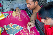 Craftsmen performing embroidery work on a Saree. Photographed in Ahmedabad, Gujarat, India