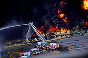 Savannah firefighters use a ladder truck to battle a blaze in a warehouse at the Georgia Ports Authority Ocean Terminal, Saturday, Feb. 8, 2014, in Savannah, Ga. (AP Photo/Stephen B. Morton)