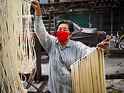 "29 DECEMBER 2018 - BANGKOK, THAILAND: A woman hangs longevity noodles out to dry in front of her family shophouse. The family has been making traditional ""mee sua"" noodles, also called ""longevity noodles"" for three generations in their home in central Bangkok. They use a recipe brought to Thailand from China. Longevity noodles are thought to contribute to a long and healthy life and  are served on special occasions, especially Chinese New Year, which is February 4, 2019. These noodles were being made for Chinese New Year.     PHOTO BY JACK KURTZ"