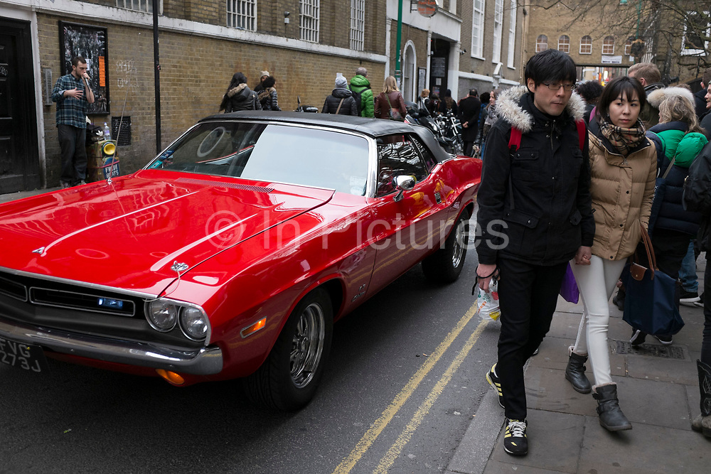Street scene as an red American classic vintage car passes on Brick Lane Market in the East End of London, UK. This area is known for it's eclectic, brilliant, sometimes bizarre fashion as young people meet up on Sunday, market day, and time for people to gather, hang out, and maybe find a bargain.