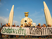 """19 SEPTEMBER 2015 - BANGKOK, THAILAND:  Anti coup protestors with a banner that says """"Long live the people, down with dictatorship"""" gather at Democracy Monument in Bangkok. Hundreds of people protested against Thailand's military dominated government Saturday. The protest started with seminar about the 2006 coup that deposed popularly elected former Prime Minister Thaksin Shinawatra. After the seminar activists marched from Thammasat University to Democracy Monument, about 1 mile. Political gatherings of more than 5 people are banned by Thailand's military government and police tried to dissuade the protestors from finishing their march. Protestors ignored the police, who then stood by and watched but made no effort to intervene. At Democracy Monument protestors laid flowers and made speeches against the military. It was the largest anti-coup protest in Bangkok in more than a year.    PHOTO BY JACK KURTZ"""
