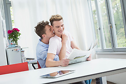 Homosexual couple embracing each other while reading newspaper, smiling