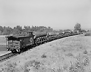"""Ackroyd 06955-15. """"Batten, Barton, Durstine & Osburn. Logs at Northern Pacific side track, Vancouver, Washington. June 25, 1956"""" Northern Pacific logging train, caboose end view"""