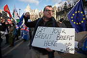 Anti Brexit protester with a placard reading Get your Brexit benefit here as a satire of the plan to potentially let Big Ben chime at midnight on 31st January, this protester is ringinga small bell for £5 instead of the £500,000 it is said it will cost to bring the chime back for the 31st at Westminster outside Parliament on 15th January 2020 in London, England, United Kingdom. With a majority Conservative government in power and Brexit day at the end of January looming, the role of these protesters is now to demonstrate in the hope of the softest Brexit deal possible.