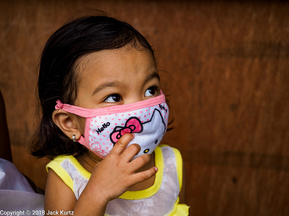 """22 JANUARY 2018 - GUINOBATAN, ALBAY, PHILIPPINES: A child in Guinobatan wears a face mask because of an ash fall caused by the eruption of Mayon volcano. Several communities in Guinobatan were hit ash falls from the eruptions of the Mayon volcano and many people wore face masks to protect themselves from the ash. There were a series of eruptions on the Mayon volcano near Legazpi Monday. The eruptions started Sunday night and continued through the day. At about midday the volcano sent a plume of ash and smoke towering over Camalig, the largest municipality near the volcano. The Philippine Institute of Volcanology and Seismology (PHIVOLCS) extended the six kilometer danger zone to eight kilometers and raised the alert level from three to four. This is the first time the alert level has been at four since 2009. A level four alert means a """"Hazardous Eruption is Imminent"""" and there is """"intense unrest"""" in the volcano. The Mayon volcano is the most active volcano in the Philippines. Sunday and Monday's eruptions caused ash falls in several communities but there were no known injuries.    PHOTO BY JACK KURTZ"""
